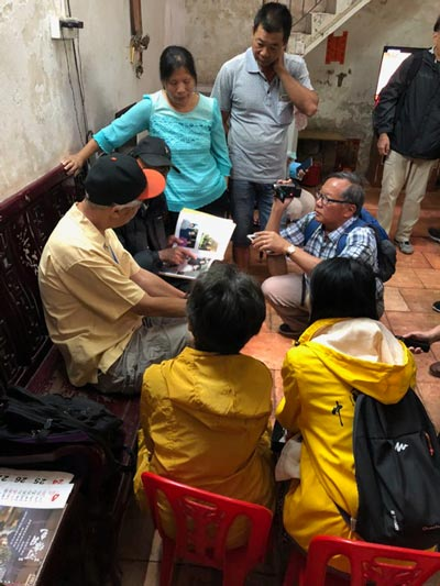 gordon chin looking at photos with his nephew who is village chief